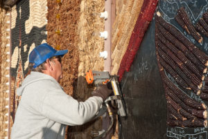 Dan McCloud is one of some 20 people needed to install murals on the Corn Palace.
