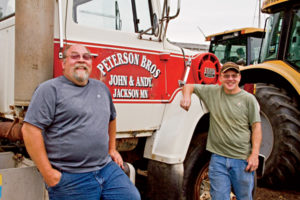 "John and Andy Peterson: ""One of the things our enterprise has had to focus on, especially because we work, is efficiency,"" says John Peterson. ""We're relatively small in the scheme of things, but the guys who are farming 2,000, 3,000, 5,000, 20,000 acres are facing those same issues, just for different reasons."" Above: John (left) and Andy on their farm. Longtime Challenger users, they're now looking to add Massey Ferguson tractors to their operation. Below, Andy and John at the plant."