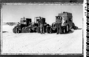 Sir Edmund Hillary, right, and Jim Bates, both of New Zealand, stand before their tractors on Jan. 4, 1958, after arrival at the American Scientific Station at the South Pole. The party of five travelled 1,200 miles with this equipment over polar snow and ice. The square box at right was Hillary's quarters and housed the expedition's radio equipment.