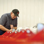 Larry works on a planter in his farm shop.