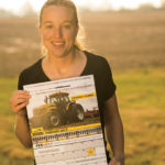 Emma shows off the McAllister Ag calendar that features her farm and tractor.