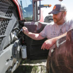 A man performs maintenance on a Massey Ferguson brand tractor