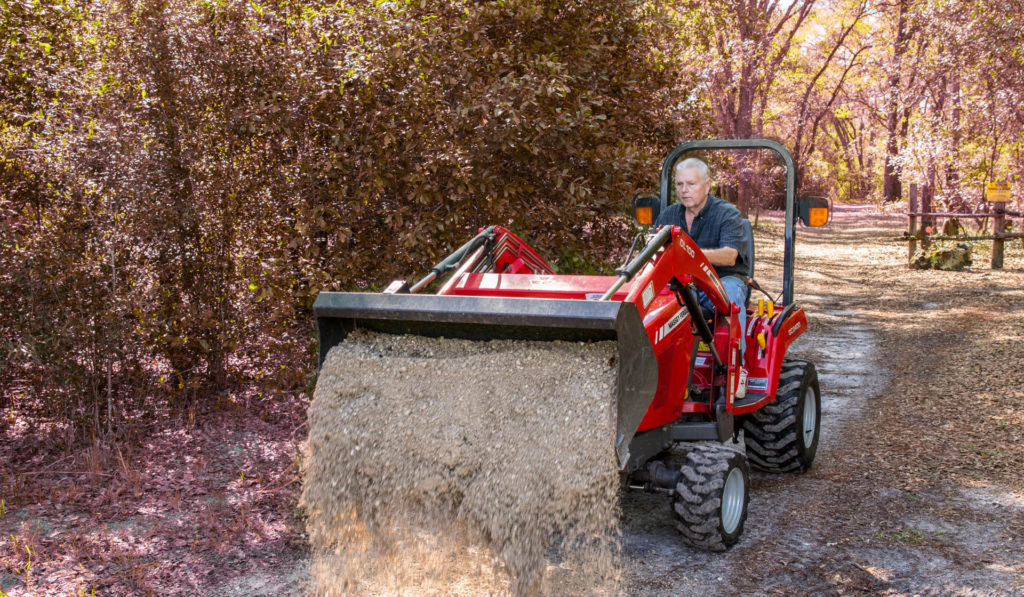 Man uses a Massey Ferguson front loader tractor to dump fresh gravel on a road to protect it during the winter.