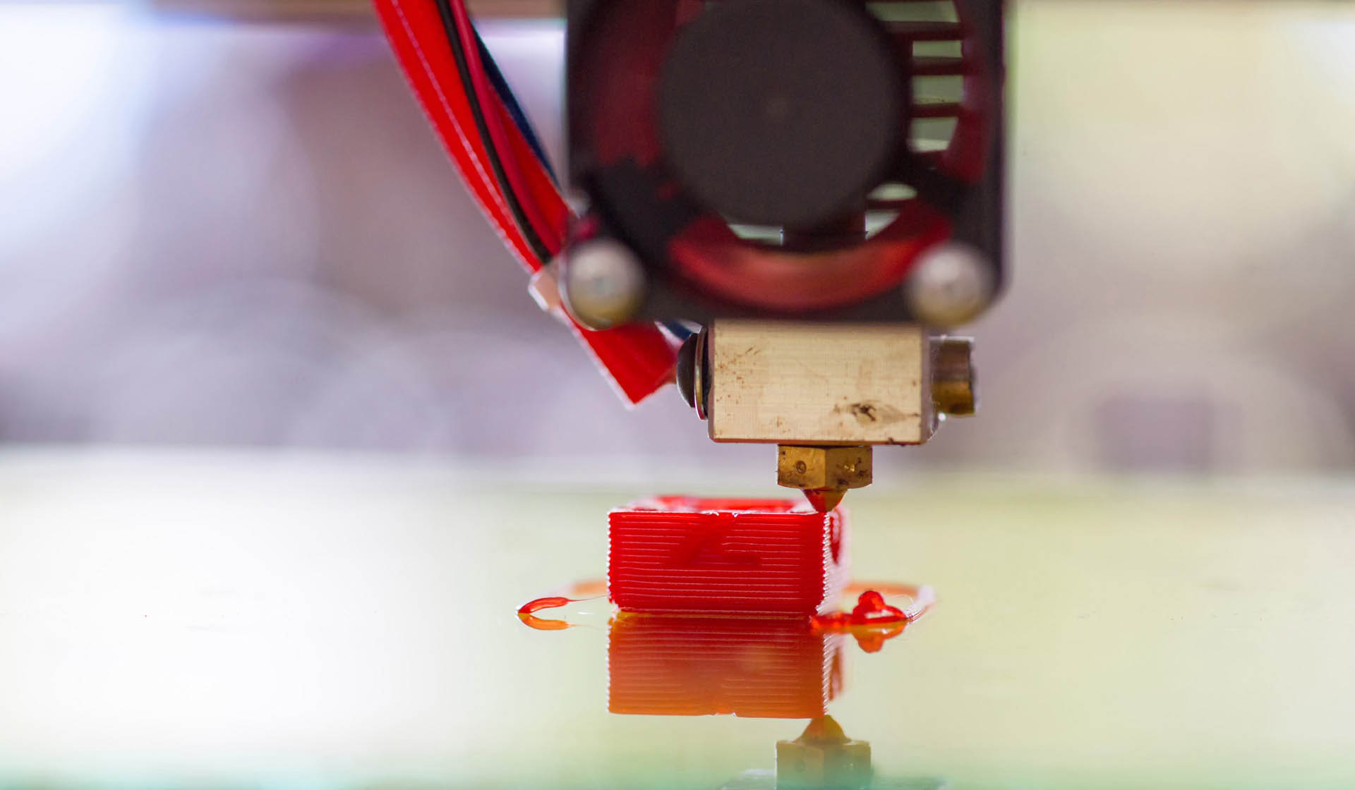 A 3D printer creates a small red part that will be used in the manufacturing of farming equipment.