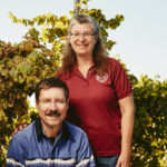 Jim and Ann Gardner take a moment with their dog to stand in their Vineyard in Arizona.
