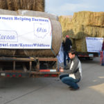 Luke Dull of Montgomery County secures a Farmers Helping Farmers sign on the back of his hay load that is headed to farms in need.