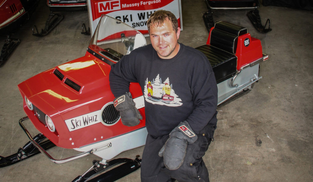 Jason Johnson with one of his vintage Massey Ferguson Ski Whiz snowmobiles.