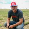 Steve Hicks kneels down on his farm in Indiana.