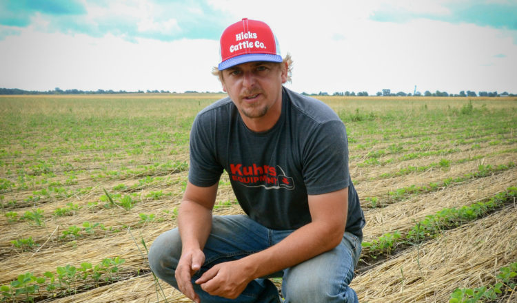 Steve Hicks kneels down on his farm in Indiana.