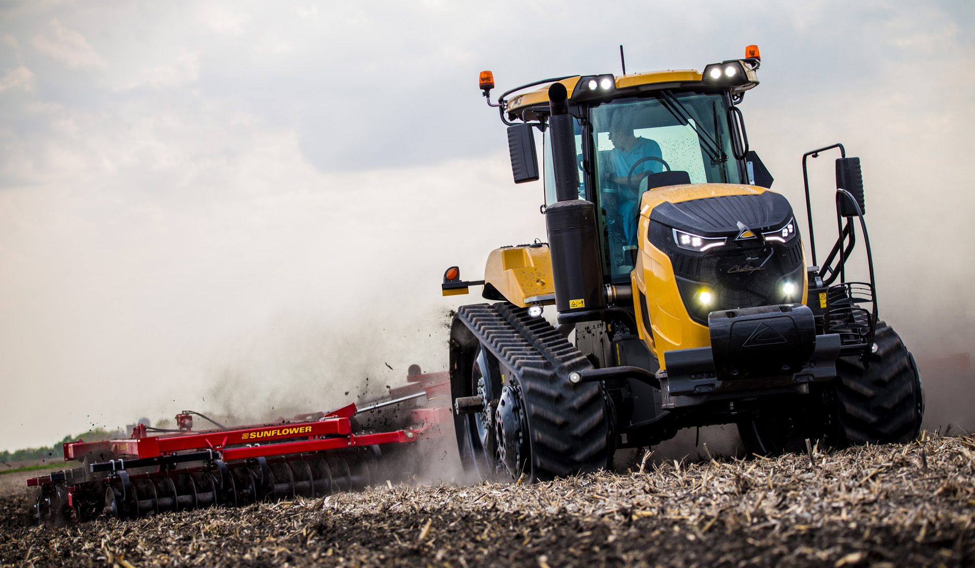 The new Challenger MT700 track tractor is shown pulling a tiller over farmland.