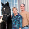 Sonia and Jimmy Smithers stand smiling with their horse, Patch.