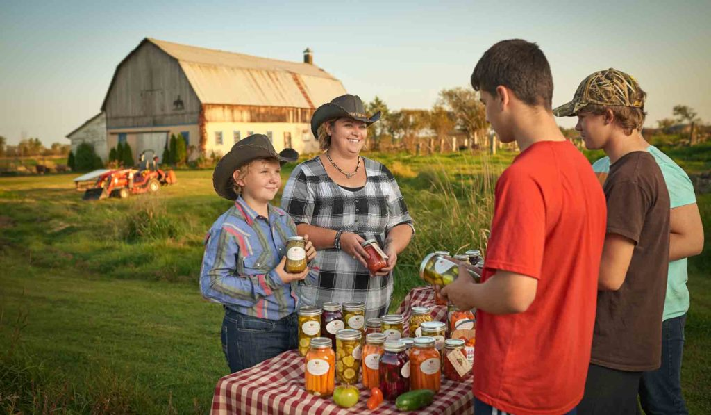 Austin and Marj Wilkie sell their colorful jars to passersby as the sun sets.