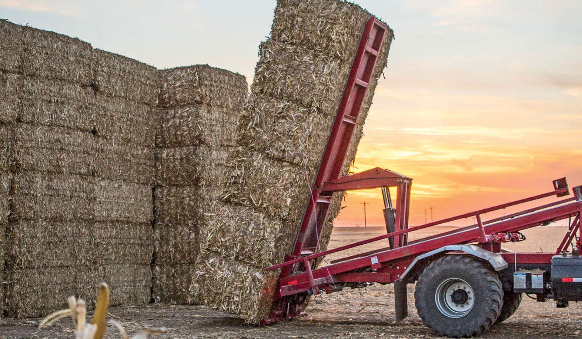 Bales of hay, stacked high, are placed in a neat pile by machine.