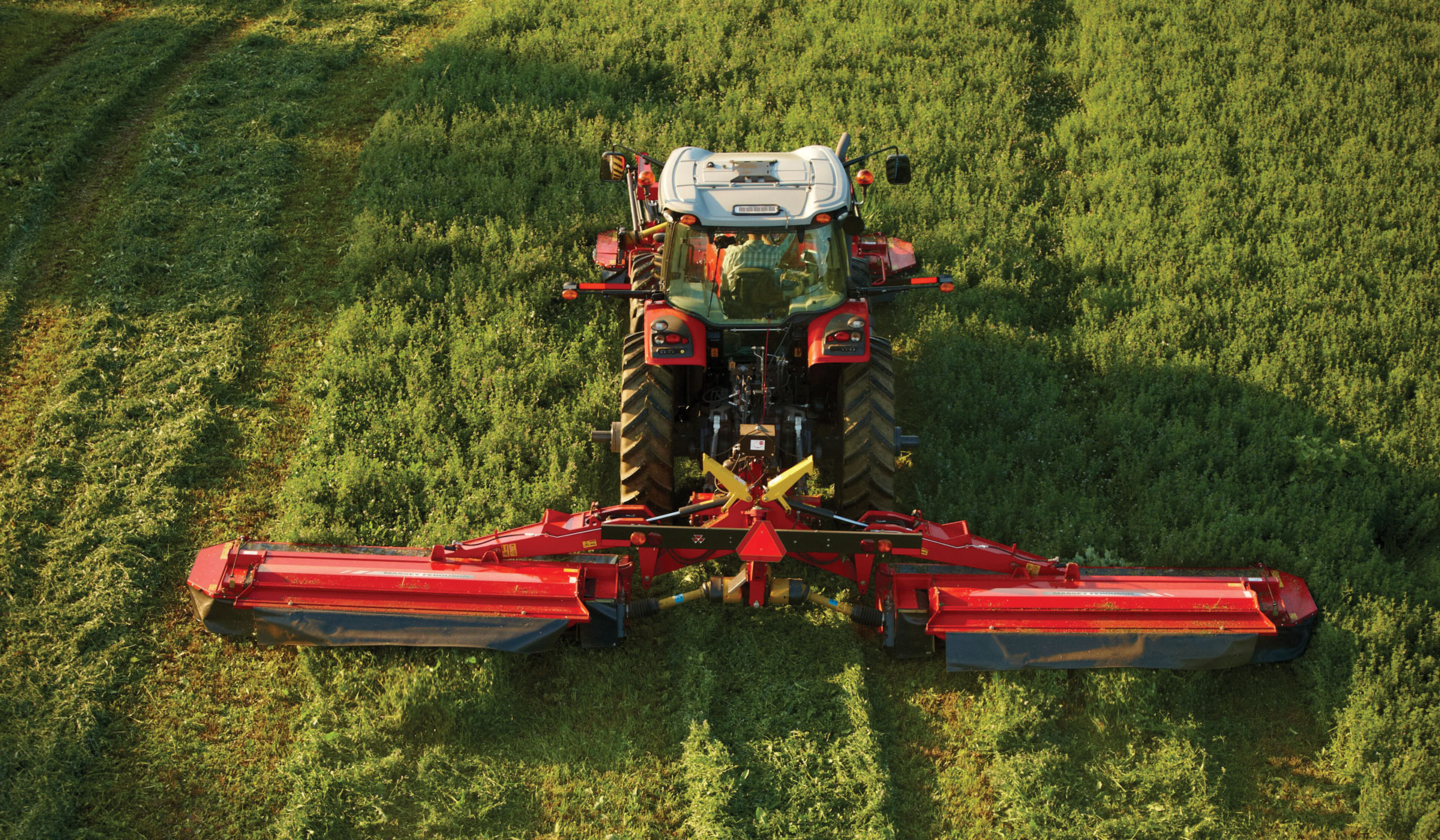 A Massey Ferguson DM series triple mower cuts through high grass in a field.