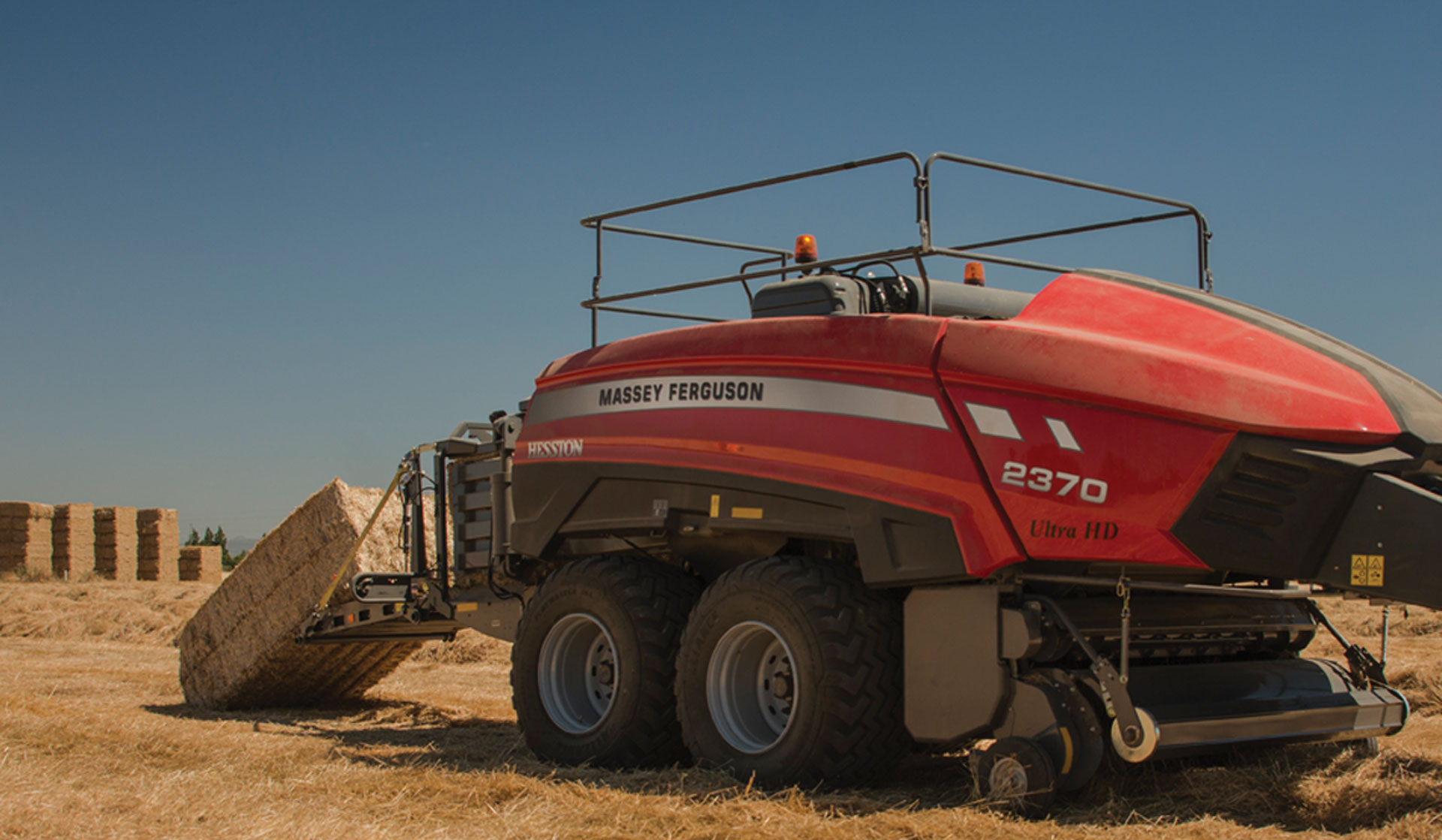 The Massey Ferguson 2370 Ultra HD Large Square Baler produces a golden bale of hay.