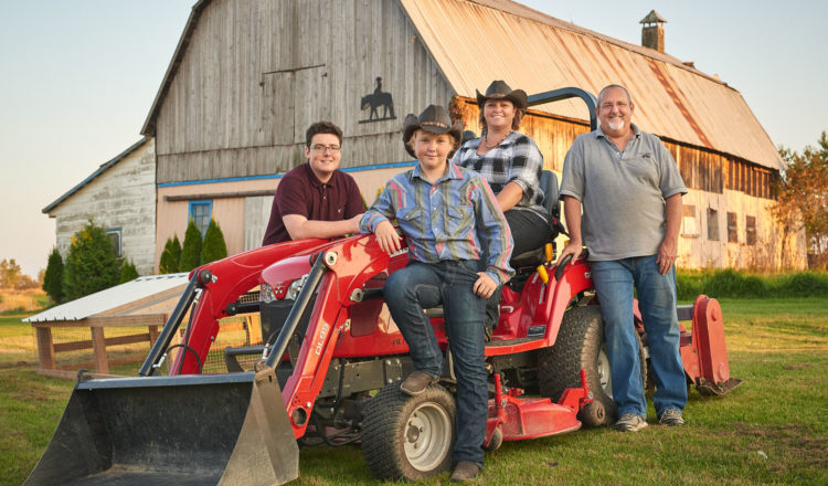 The Wilkie Family stands in front of their subcompact Massey Ferguson® GC1715 on their Ontario farm.