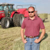 Farmer Rex Reyher stands in front of his red Hesston by Massey Ferguson 2270 baler.